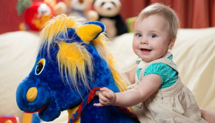 baby and toddler enjoy rocking horse and rides on toys